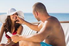 Der gutaussehende Mann, der Sonnencreme auf seinen Freundinnen aufträgt, riechen Stockfoto