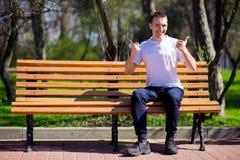 Der gutaussehende Mann, der in Park geht und sitzt auf Bank und Wartefreundin stockfoto