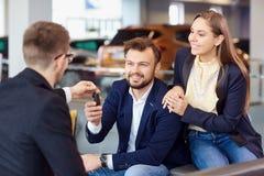 Der Händler gibt dem Kunden die Schlüssel zum Neuwagen stockfoto