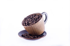 Der hölzerne Becher, der mit Kaffeebohnen und Kaffeebohnen gefüllt wurde, zerstreute O Stockfotografie