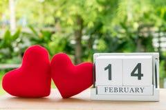 Der hölzerne Kalender am 14. Februar kennzeichnet zwei rote Herzen, die nebeneinander mit einem natürlichen Hintergrund gesetzt w lizenzfreie stockfotos