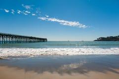 Der hölzerne Pier auf dem Meer mit dem Strand lizenzfreie stockbilder