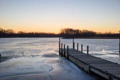 Der hölzerne Pier, der in Eis verlängert, bedeckte See bei Sonnenuntergang lizenzfreies stockfoto