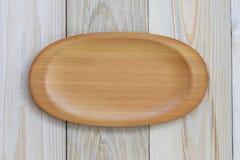 Der hölzerne Teller, der auf Holzfußboden leer ist und haben Kopienraum lizenzfreies stockfoto