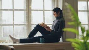 Der hübsche Brunette in der Strickjacke und in den Jeans ist das Lesebuch, das auf Fensterbrett am Weihnachtstag soliture genieße stock video footage