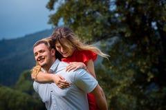 Der hübsche glückliche Mann gibt der Doppelpolfahrt seine bezaubernde lächelnde blonde Freundin am Hintergrund von Stockfotografie
