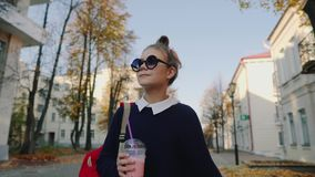 Der hübsche Hippie, der mit roter Tasche jugendlich ist, trinkt Milchshaken von einer gehenden Straße der Plastikschale zwischen  stock video
