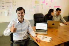 Der hübsche hohe und lächelnde Geschäftsmanndaumen, sitzt er auf dem Stuhl im Büro, erfolgreiches Konzept lizenzfreie stockbilder