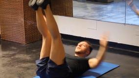 Der hübsche junge Mann, der ABS tut, trainiert auf Matte stock footage
