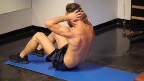Der hübsche junge Mann, der ABS tut, trainiert auf Matte stock video footage