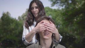 Der hübsche junge Mann mit den Klammern und langem Haar, die im Vordergrund, seine Freundin sitzen, kommt von hinten und stock video footage