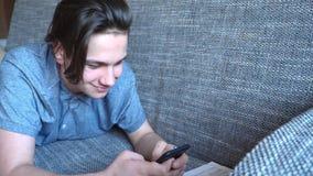 Der hübsche Jungenjugendliche, der am Telefon spricht, sitzt auf einem grauen Sofa lizenzfreie stockfotografie
