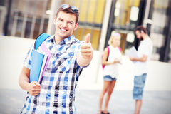 Der hübsche Student, der o.k. darstellt, unterzeichnen herein den Campus lizenzfreies stockbild