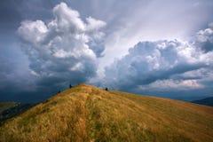 Der Hügel in den Bergen auf Hintergrund von drastischen Himmelsturmwolken Stockbild