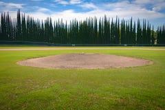 Der Hügel des Werfers mit Baseball - Zypresse-Außenfeld-Wand stockfoto