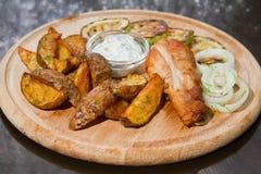 Der Hühnerschenkel, der mit der Zucchini, gedient mit Pommes-Frites gegrillt wurde, legte Zwiebeln, weiße Soße und Dill auf hölze stockbild