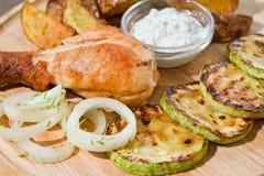 Der Hühnerschenkel, der mit der Zucchini, gedient mit Pommes-Frites gegrillt wurde, legte Zwiebeln, weiße Soße und Dill auf hölze stockfotografie