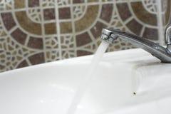 Der Hahn wurde in der Zahnbürste gelassen Viel Wasser zu verlieren ist unnötig Lassen Sie ` s Abwehrwasser stockbilder