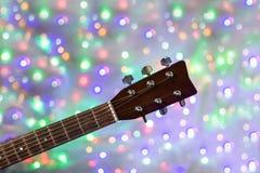 Der Hals der Akustikgitarre auf Weihnachtslicht bokeh Hintergrund Stockbild