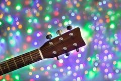 Der Hals der Akustikgitarre auf Weihnachtslicht bokeh Hintergrund Stockbilder
