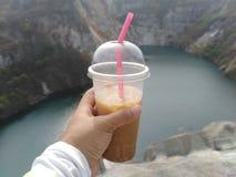 In der Hand, die eine Kaffeetasse mit einer schönen Ansicht hält stockfotografie