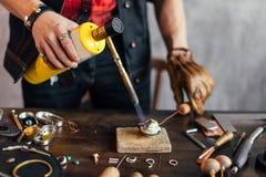 Der Handwerker, der das Metall erhitzt, schließen herauf Foto stockfoto