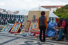 Der Handwerker, der neugierige Junge und Lissabon an ihren Füßen Stockbild