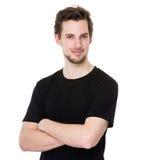 Der hübsche junge Mann, der mit den Armen lächelt, kreuzte auf weißem Hintergrund Stockfotografie