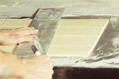 Der Hefeteig, der zu den Stücken für die Herstellung cuted ist, backt Lizenzfreie Stockbilder