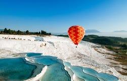 Der Heißluftballon, der über Travertin fliegt, vereinigt Kalksteinterrassen stockfoto