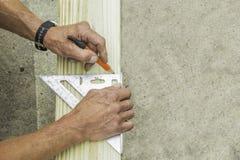 Der Heimwerker markiert das Brett mit einem Bleistift und einem Quadrat stockfotos
