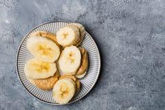 Der helle gesunde Snack, der von den Bananen-Scheiben gemacht werden und der Acajoubaum bestreichen mit Butter Lizenzfreies Stockbild