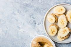 Der helle gesunde Snack, der von den Bananen-Scheiben gemacht werden und der Acajoubaum bestreichen mit Butter Stockbilder