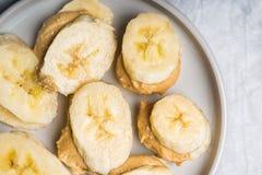 Der helle gesunde Snack, der von den Bananen-Scheiben gemacht werden und der Acajoubaum bestreichen mit Butter Lizenzfreies Stockfoto