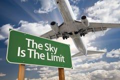 Der Himmel ist das Grenzgrün-Verkehrsschild und das Flugzeug Stockfotografie