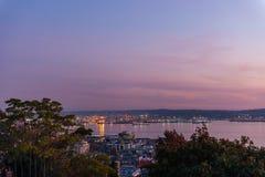 Der Himmel nimmt auf einem purpurroten Ton an der Dämmerung im Hafen von Seattle und von Elliott Bay stockfotos