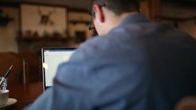 Der hintere viewof Freiberuflergeschäftsmann, der an Laptop mit Diagrammen auf Schirm im Café und trinkt arbeitet dann, Tasse Kaf stock video footage
