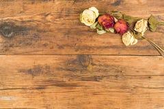 Der Hintergrund, der mit Gelbem und Rot hölzern ist, verwelkte Rosen in einem bouqet Stockbild