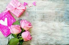 Der Hintergrund des Valentinsgrußes mit einem Geschenk, einer Blume und einer Karte lizenzfreie stockbilder