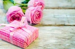 Der Hintergrund des Valentinsgrußes mit Geschenk und Blumen stockfotos