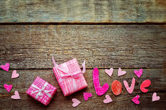 Der Hintergrund des Valentinsgrußes mit Geschenk und Wort Liebe lizenzfreie stockbilder