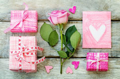 Der Hintergrund des Valentinsgrußes mit Geschenke, Blume und Karte stockfotos