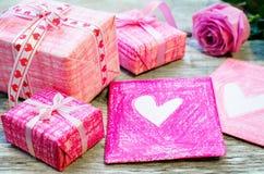 Der Hintergrund des Valentinsgrußes mit Geschenken, Blume und Karte lizenzfreies stockfoto