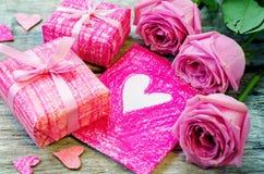 Der Hintergrund des Valentinsgrußes mit Geschenken, Blumen und Karte stockbilder