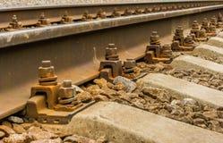 Der Hintergrund ist eine Nahaufnahme von Schienen und von Betonschwellen Lizenzfreies Stockfoto