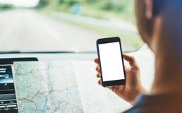 Der Hippie-Mann, der auf Navigationskarte im Auto, der touristische Reisende fährt und hält im Mann schaut, übergibt Smartphone g Lizenzfreie Stockbilder
