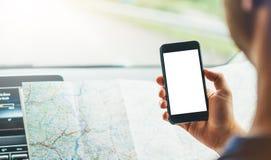 Der Hippie-Mann, der auf Navigationskarte im Auto, der touristische Reisende fährt und hält im Mann schaut, übergibt Smartphone g Stockbild