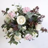 Der Hochzeitsblumenstrauß einer Braut von einer Rose, eine rosa Gartennelke, Eukalyptus auf einem Holztisch Stockfoto