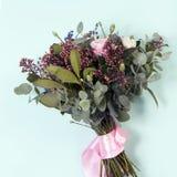 Der Hochzeitsblumenstrauß einer Braut von einer Rose, eine rosa Gartennelke, Eukalyptus auf einem Holztisch Lizenzfreies Stockfoto