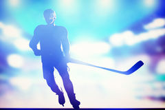Der Hockeyspieler, der auf Eis in der Arenanacht eisläuft, beleuchtet stockfoto